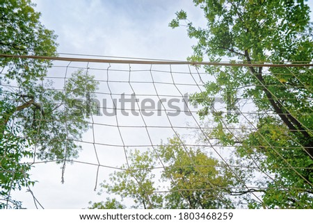 The volleyball net is on the background of the sky with clouds. The net is stretched between the trees in the yard. Concept for street sports, outdoor games and competitions. #1803468259