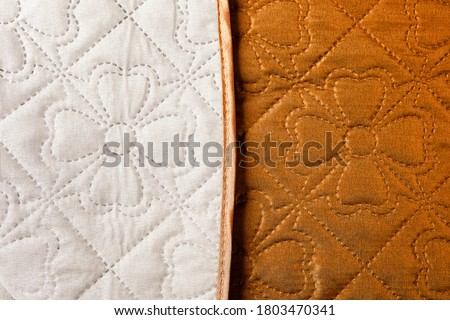 Home textile. Beige-brown bedspread. Quilted blanket. Two-tone coverlet for the  bed. Fabric with a flower pattern. Double-sided fabric product.