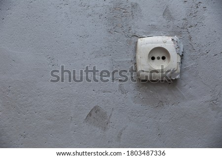 texture of gray plastered wall with old electrical power socket