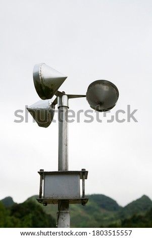Anemometer pole on cloudy sky and mountain background #1803515557