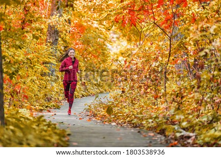 Autumn forest run path. Fall trail runner woman running in beautiful foliage woods nature background. Asian happy sports woman training outdoor.  #1803538936