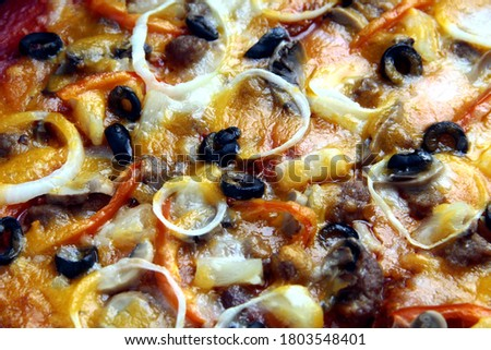 Close up photo of freshly made pizza with tomato sauce, cheese, black olives, onion, ham, mushroom and pepperoni toppings. #1803548401