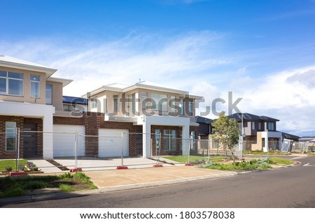 Brand new residential townhouses behind temporary construction fences in an Australian suburb. Concept of real estate development, house for sale and housing market. Melbourne, VIC Australia. Royalty-Free Stock Photo #1803578038