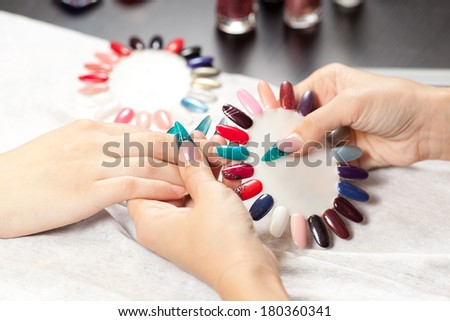 Woman at nail studio chosing color of nail polish #180360341