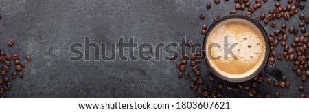 Horizontal banner with cup of coffee and coffee beans on dark stone background. Top view. Copy space - Image Royalty-Free Stock Photo #1803607621