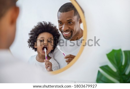 Portrait of happy family black African American father and son child boy brushing teeth in the bathroom. Morning routine with toothbrushes, father's day concept #1803679927