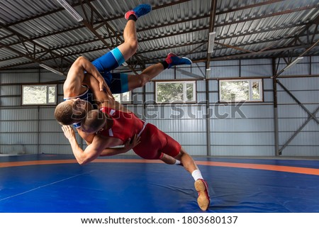 Two greco-roman  wrestlers in red and blue uniform wrestling  on a blue wrestling carpet in the gym