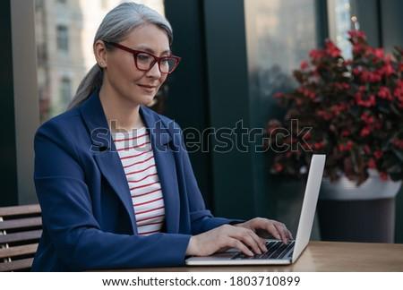 Mature businesswoman using laptop computer, working online. Portrait of middle aged asian copywriter wearing stylish eyeglasses typing on keyboard, edit something