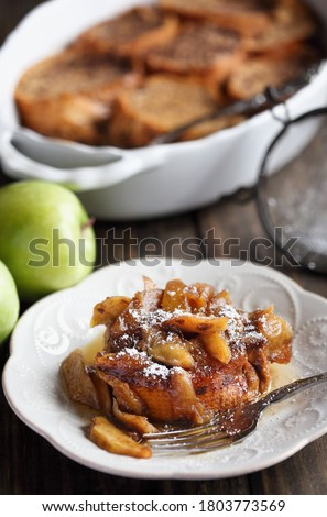 Serving of apple French toast casserole with maple syrup and powdered sugar. Selective focus with blurred background.