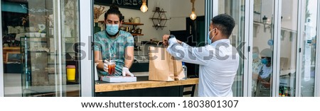 Young man with mask picking up a take away food order Royalty-Free Stock Photo #1803801307