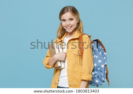 Smiling little blonde kid girl 12-13 years old wearing yellow jacket with backpack hold books isolated on pastel blue background studio portrait. Childhood lifestyle concept. Education in school. Royalty-Free Stock Photo #1803813403