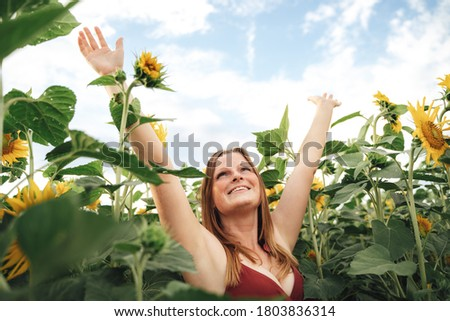 Smiling young woman with arms raised enjoying her freedom in sunflower field. High quality photo