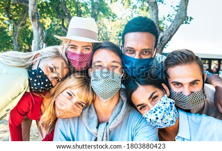 Multiracial milenial friends taking selfie with closed face masks during Covid second wave outbreak - New normal lifestyle concept with young people having fun together - Bright vivid backlight filter Royalty-Free Stock Photo #1803880423