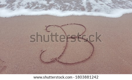 B Alphabet letters writing on the sand beach .