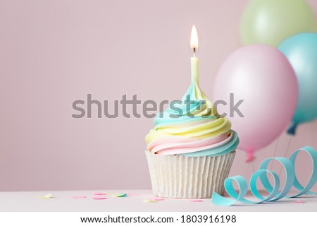 Pastel rainbow birthday cupcake with candle and balloons Royalty-Free Stock Photo #1803916198