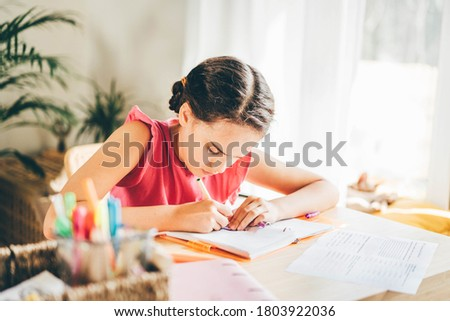Upset caucasian girl sitting at the desk and writing in a notebook and doing homework.