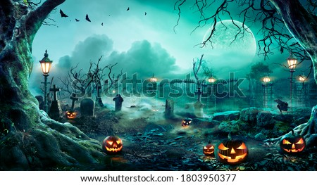 Pumpkins In Graveyard In The Spooky Night - Halloween Backdrop Royalty-Free Stock Photo #1803950377
