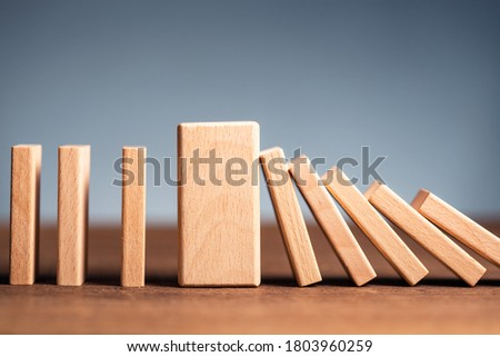 Closeup thick domino wood block in a row stop the falling, be stable in crisis, business solution concept Royalty-Free Stock Photo #1803960259