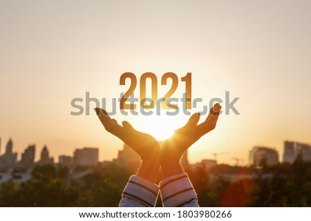 Hands show New Year 2021 against the background of the sun. #1803980266