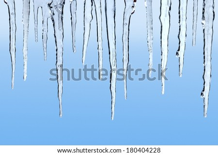 Icicles on blue background Royalty-Free Stock Photo #180404228