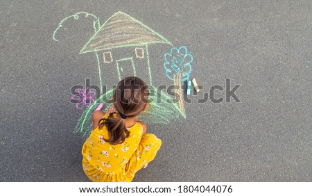 The child draws a house on the asphalt. Selective focus. kid. Royalty-Free Stock Photo #1804044076