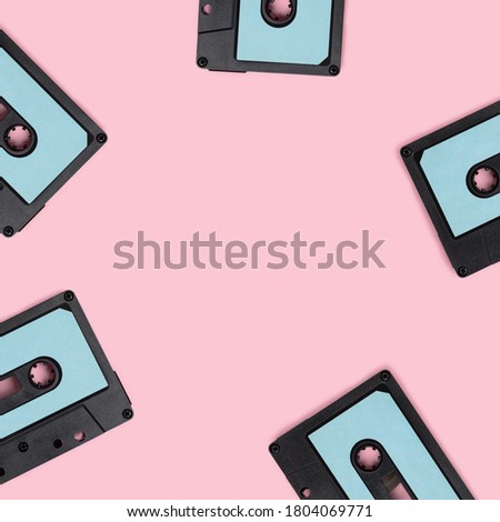 Wreath made of cassette tapes on a pink background. Creative template with place for text.