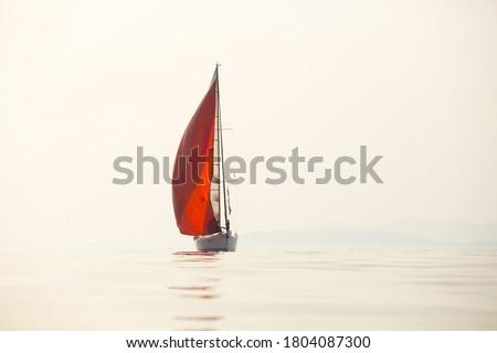 Sailing yacht at sea under an orange sail. Royalty-Free Stock Photo #1804087300