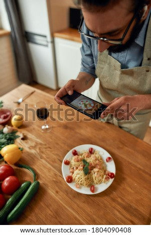 Delicious meal. Young man, cook taking picture of garlic butter shrimp pasta, meal decorated with basil and cherry tomatoes. Mediterranean cuisine concept. Focus on hands and phone. Vertical shot