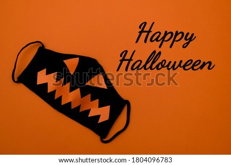 Black protective mask with orange eyes and mouth on an orange background.Happy Halloween lettering on an orange background.Halloween and covid-19 concept.Copy space for text, top view