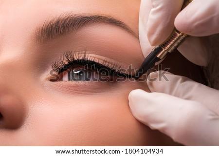 Permanent eye makeup close up shot. Cosmetologist applying tattooing of eyes. Makeup eyeliner procedure #1804104934