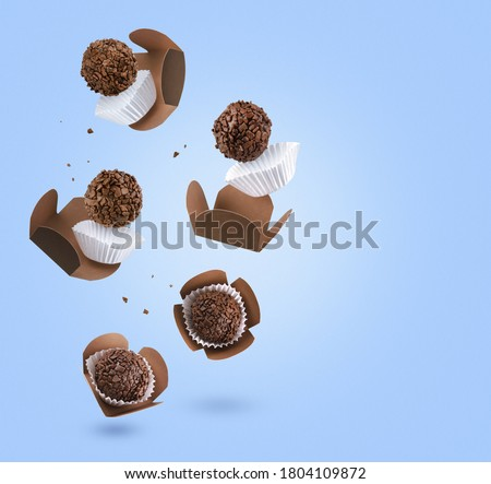 Brigadeiro (Brigadeiro), a Brazilian chocolate candy. Traditional Brazilian handmade chocolate candy. Falling in motion on blue background. Royalty-Free Stock Photo #1804109872