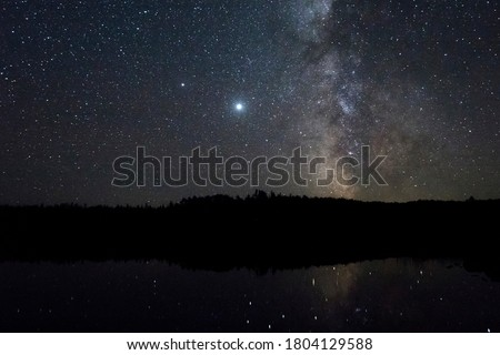 A Nighttime Long Exposure of Jupiter and the Milky Way over a Northern Minnesota Boundary Waters Landscape Royalty-Free Stock Photo #1804129588