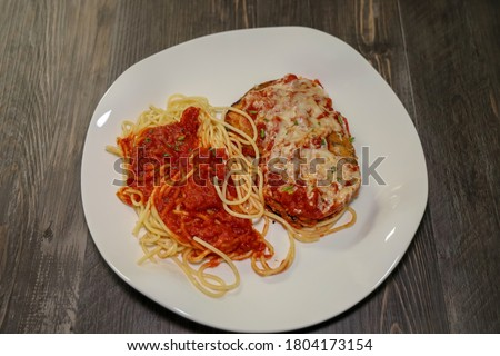 A white plate with eggplant parmesan topped with melted mozzarella cheese and spaghetti with marinara sauce.
