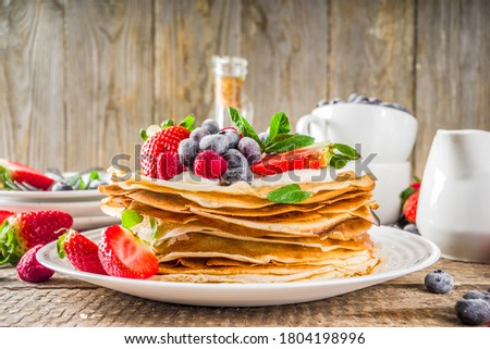 Sweet french and russian style homemade pancake crepes. Layered crepe cake with whipped cream or mascarpone cheese and fresh berries,  Royalty-Free Stock Photo #1804198996