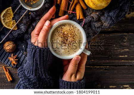 Autumn sweet hot drink, Chai Buttered Rum, Pumpkin Pie or Pumpkin Spice Coffee Latte. Cozy autumn background. Girl hold traditional latte cup in hands, on rustic wooden background #1804199011