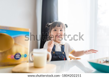 Toddler cute little asian girl drinking milk at table in kitchen.Thumb up for good milk.Cute baby girl drinking milk with milk mustache at home.Concept for food, Growth in kid, Child development. #1804202251