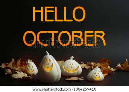 Hello October card. Jack-o-Lantern candle holders as Halloween decor and autumn dry leaves on black table