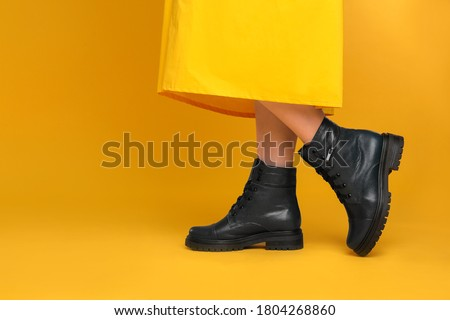 Woman wearing stylish boots on yellow background, closeup. Space for text Royalty-Free Stock Photo #1804268860