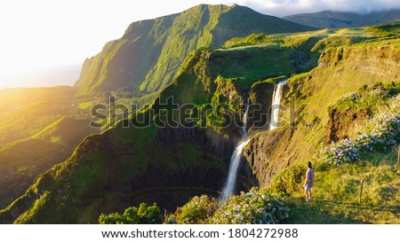 Lush paradise views over green valley, dramatic cliffs and cascading waterfall at Flores Island, The Azores, Portugal Royalty-Free Stock Photo #1804272988
