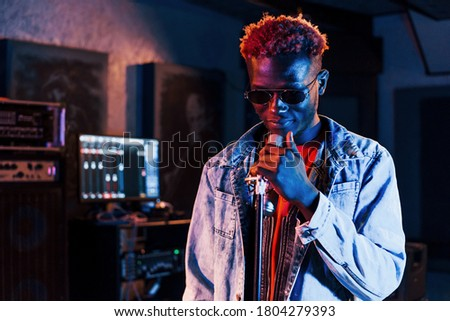 Young african american performer rehearsing in a recording studio. Royalty-Free Stock Photo #1804279393