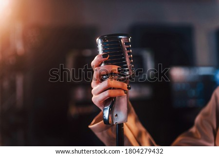 Close up view of microphone. Young beautiful female performer rehearsing in a recording studio. Royalty-Free Stock Photo #1804279432