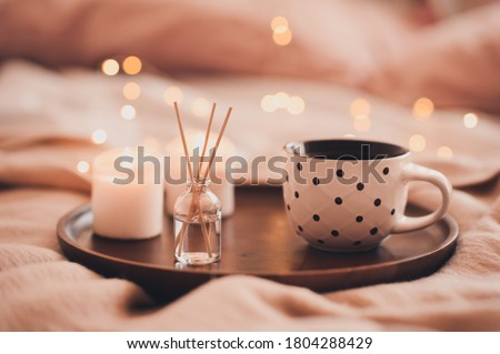 Cup of tea with aroma sticks and burning candles in bed staying on wooden tray closeup. Good morning. Winter holiday season. Cozy atmosphere.  Royalty-Free Stock Photo #1804288429