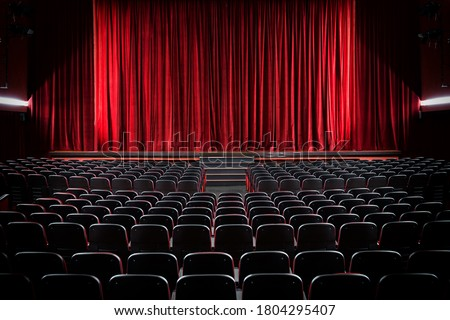 Darkened empty movie theatre and stage with the red curtains drawn viewed over rows of vacant seats from the rear Royalty-Free Stock Photo #1804295407