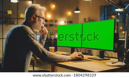 Creative Middle Aged Designer Sitting at His Desk Uses Desktop Computer with Two Green Mock-up Screens. Professional Office Employee Working Late in the Evening in His Studio