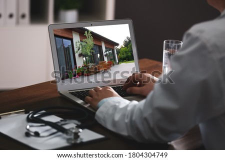 Real estate agency online service. Doctor choosing new house via laptop, closeup Royalty-Free Stock Photo #1804304749