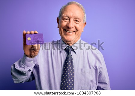 Senior grey haired business man holding credit card over purple background with a happy face standing and smiling with a confident smile showing teeth