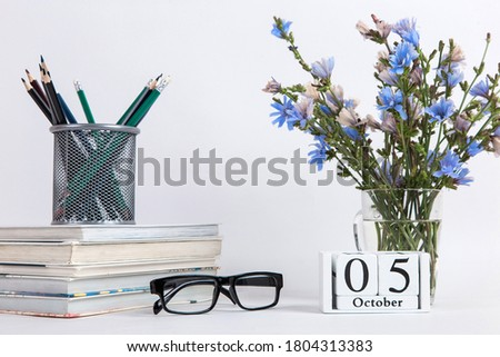 Flowers in a glass cup, books, glasses and calendar with the date of October 5, on a white background, the concept of the day teacher.