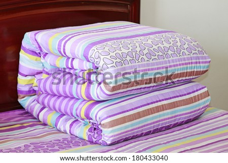 fold the quilt on the bed, closeup of photo #180433040