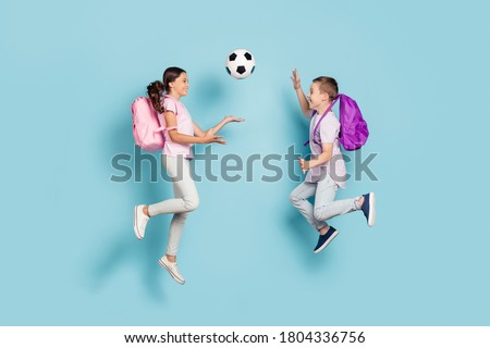 Full length body size view of two attractive small little cheerful friends friendship jumping play soccer cup goal throwing ball hobby leisure isolated blue pastel color background Royalty-Free Stock Photo #1804336756