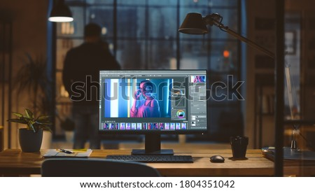 Desktop Computer with Photo Editing Software Standing on the Desk in the Modern Creative Office. In the Background Designer Drinks from a Cup Looks at the Night City out of the Window.